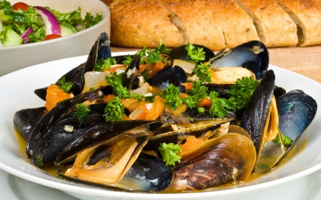 close-up of a bowl of steamed mussels served with bread and a salad
