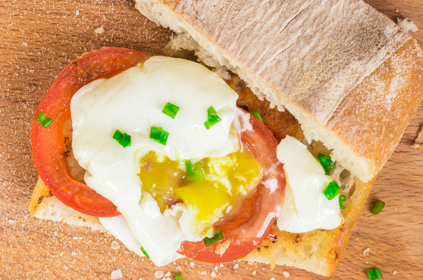 open ciabatta sandwich with tomatoes, chives, and a runny egg