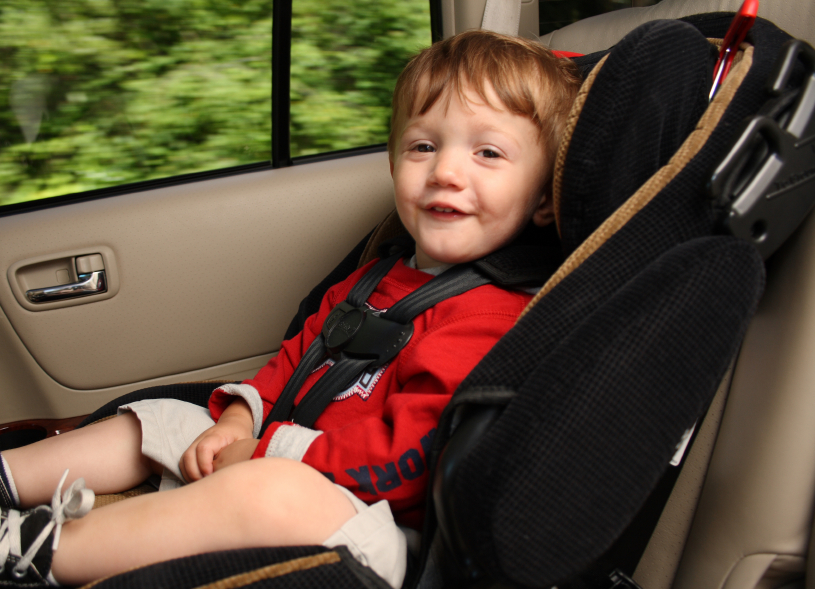 smiling toddler sitting in a front-facing car seat