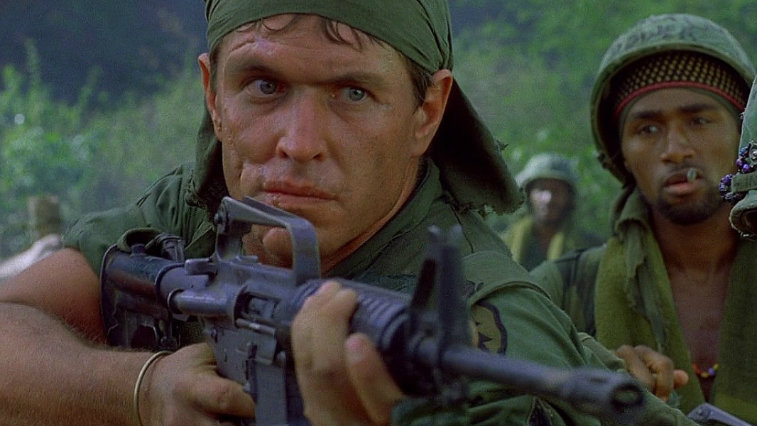 Tom Berenger holding a gun in Platoon.
