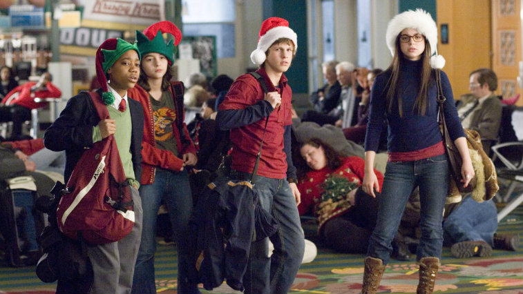The cast of Unaccompanied Minors are wearing Santa hats and are carrying bags.