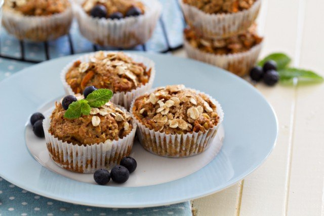 three carrot and banana oatmuffins with blueberries on a blue-rimmed plate