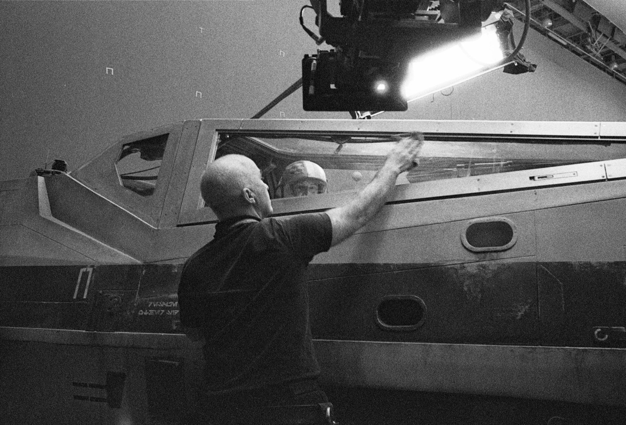 A man wipes down an X-Wing in a black and white photo