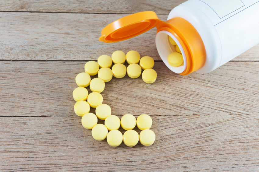 orange-yellow pills being poured from a bottle in the shape of a C