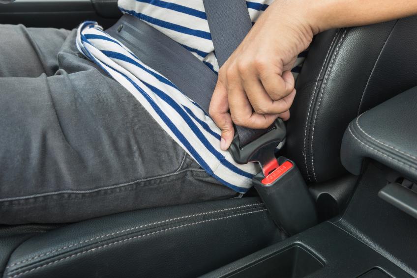 Young man fastening seat belt
