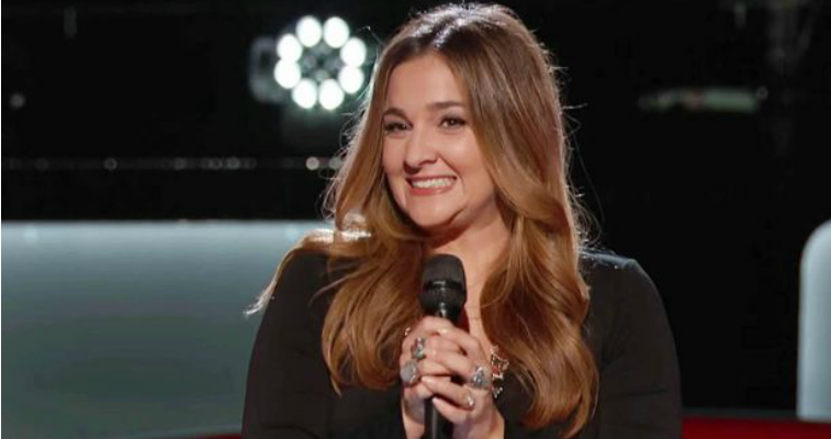 Alisan Porter is smiling and holding a microphone on The Voice.