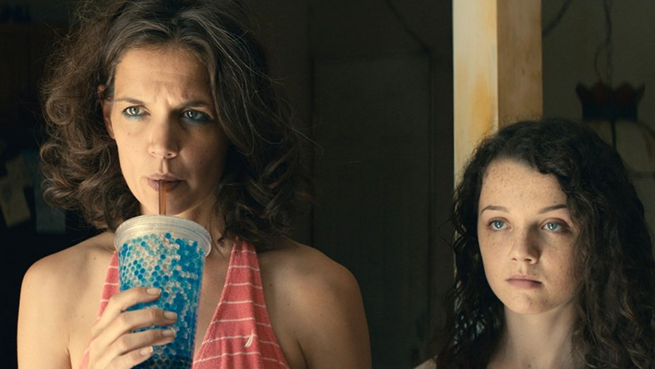 Katie Holmes sips on a soda next to a young girl in a scene from All We Had