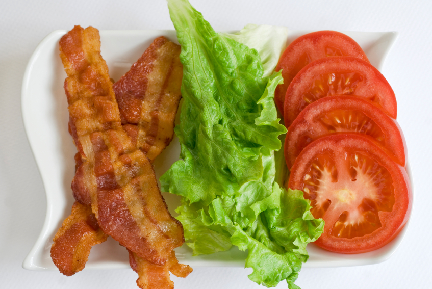 bacon, lettuce and sliced tomatoes on a white plate