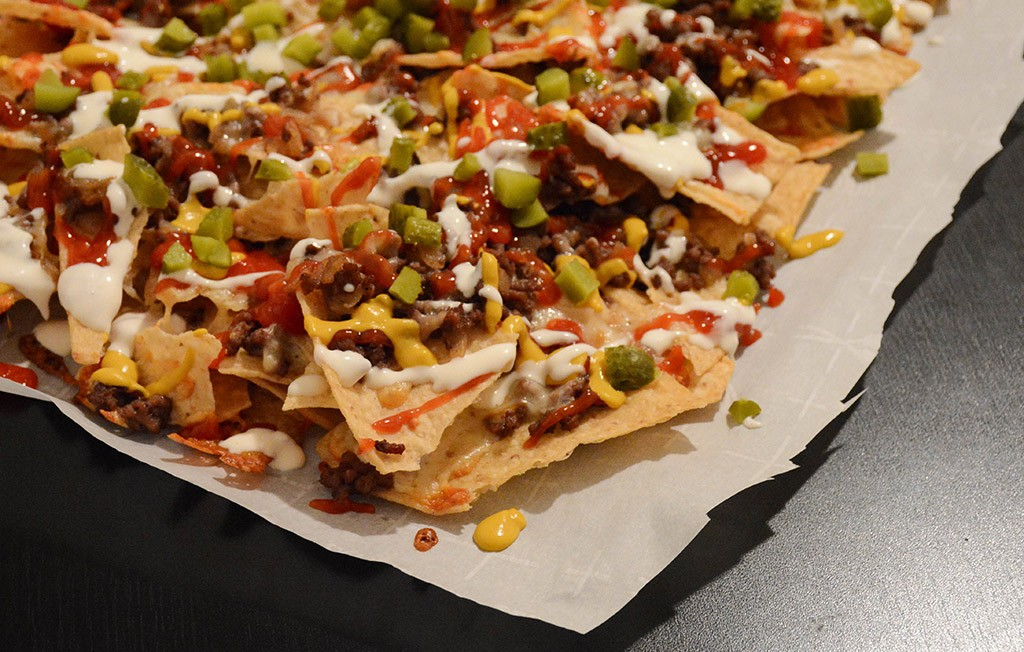 nachos with cheeseburger toppings on parchment paper