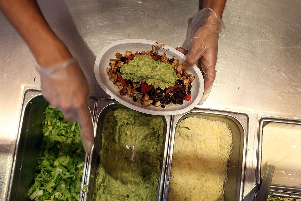 employee assembling a burrito bowl with guacamole at a Chipotle