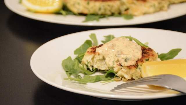one crab cake with remoulade missing a bite