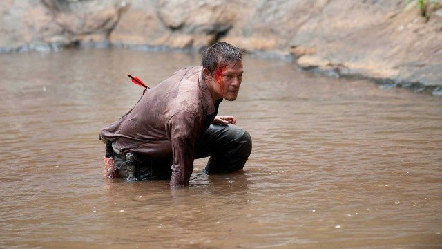 Daryl (Norman Reedus), shot with an arrow, wades through a stream in a scene from 'The Walking Dead' episode 'Chupacabra'