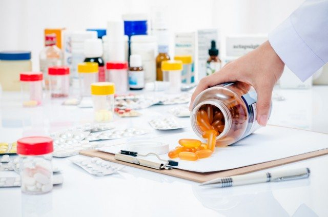 Man pouring out pills from a supplement container with more pill bottles in the background