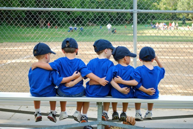 group of young boys with their arms around each other as they sit on a bench during a baseball game