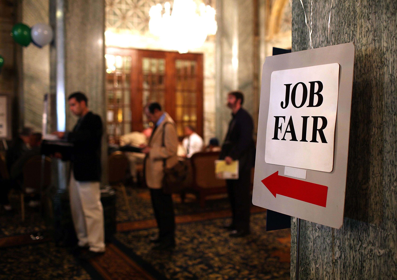 Job seekers wait in line to enter a job fair
