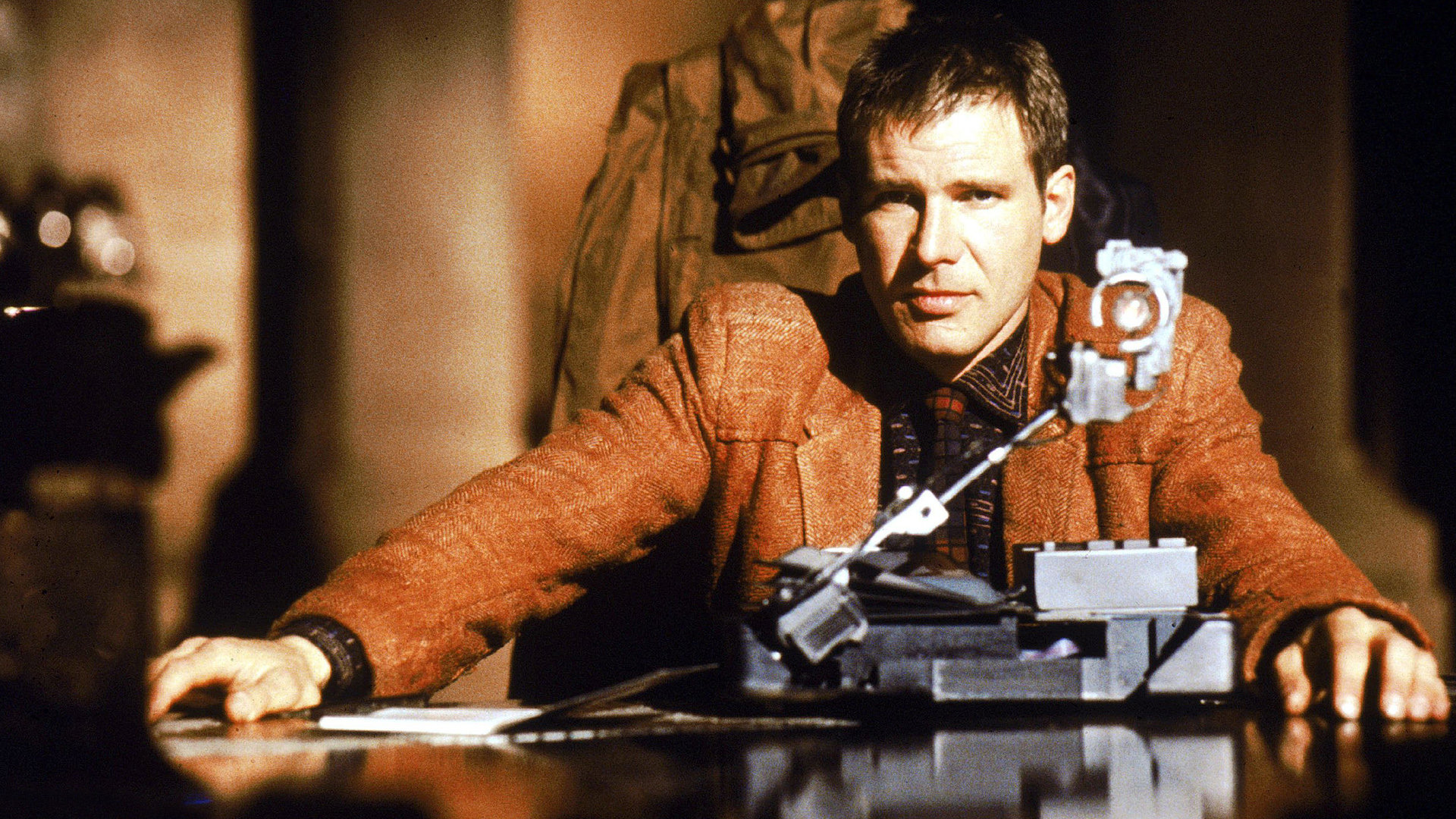 Harrison Ford sits at a desk in front of a machine