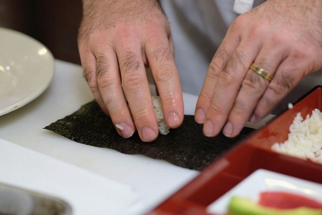 A man places a small amount of rice on seaweed while making sushi