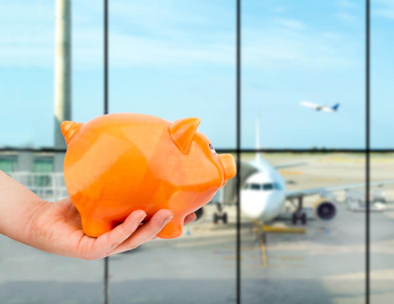 man holding a piggy bank at airport