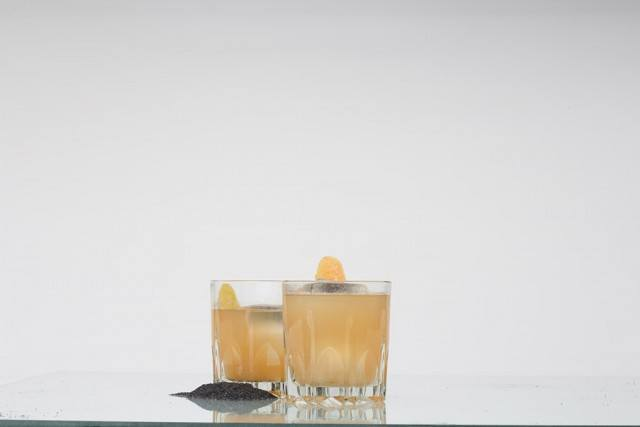 collection of short glasses filled with a banana, orange, and whiskey cocktail