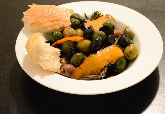 warm orange-rosemary olives in a shallow bowl with torn bread