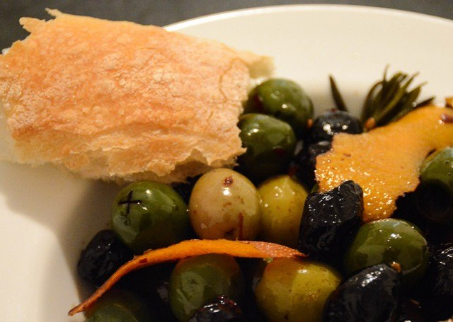 close-up of warm orange-rosemary olives in a bowl