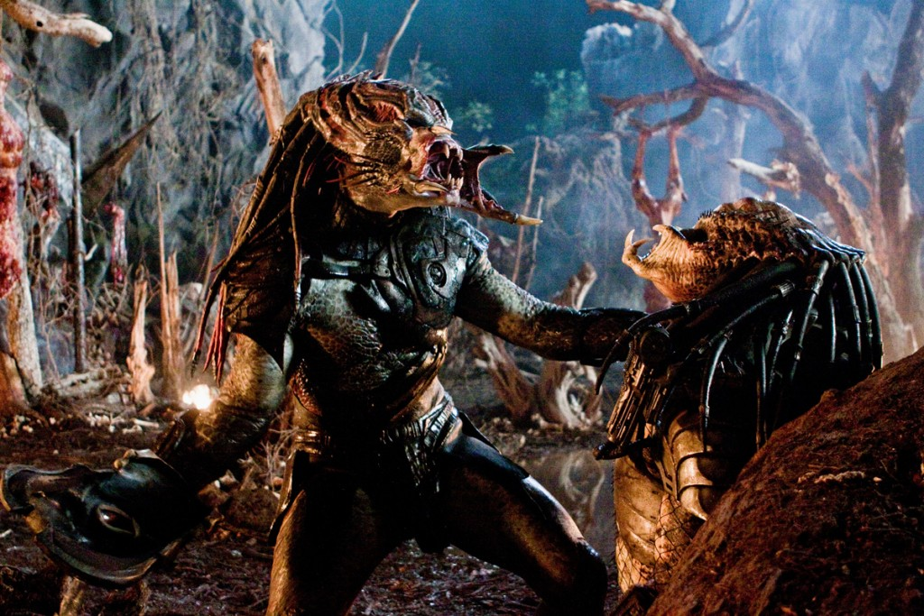 Two Predators battling, with one yelling and holding the other by the neck
