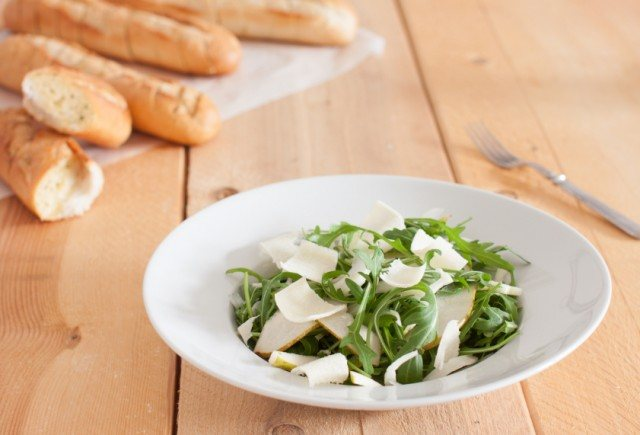 Salad of arugula on a white plate.