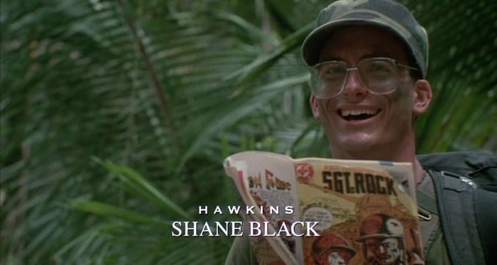 Shane Black holding a comic book, wearing large glasses and smiling