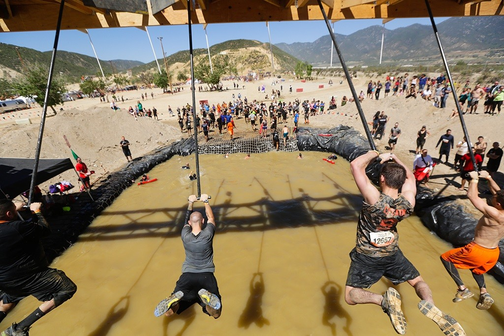 group of men swinging out over a pool of water at Tough Mudder