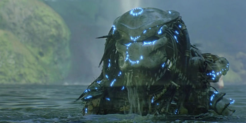 The Predator slowly rises out of a lake, with blue lights all over him
