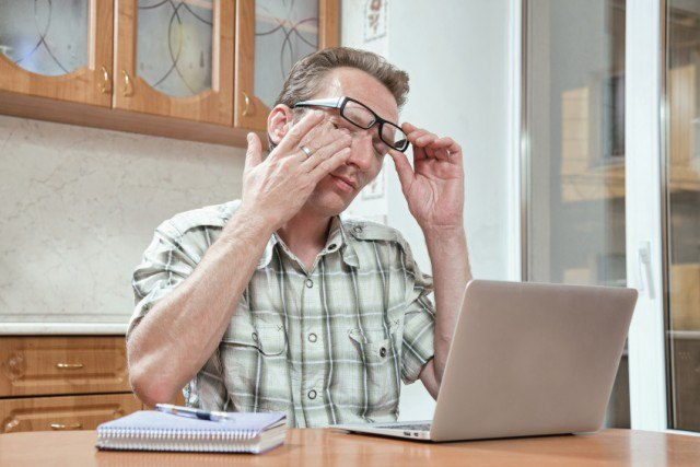 man rubbing his eyes while he works on a laptop