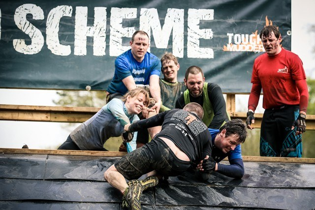people helping each other over a Tough Mudder obstacle