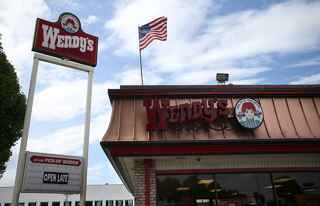 storefront at Wendy's with an American flag blowing in the wind