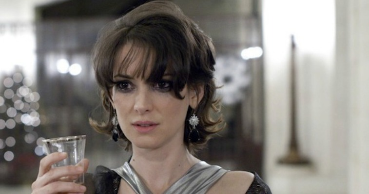 Winona Ryder is holding a wine glass as she is wearing a gown.