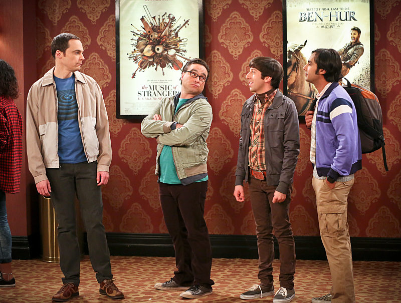 Jim Parsons, Johnny Galecki, Simon Helberg, and Kunal Nayyar stand in line in a scene from CBS's The Big Bang Theory