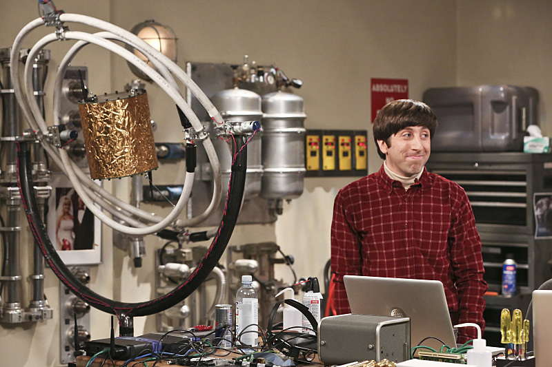 Simon Helberg as Howard Wolowitz stands in front of a computer in a red plaid shirt