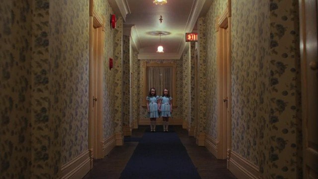 Two young girls stand at the end of an Overlook Hotel hallway in an iconic scene from Stanley Kubrick's 'The Shining.'