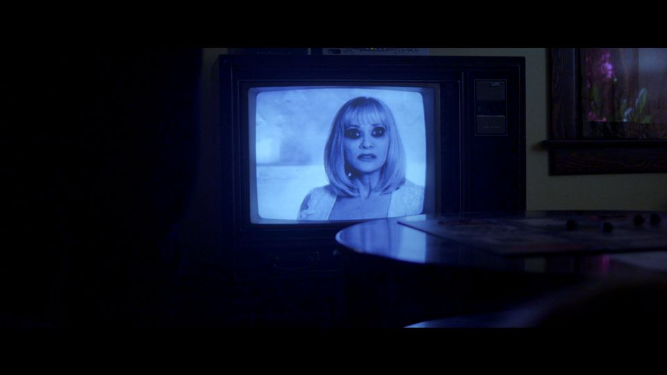 A woman on a TV screen in a dark room in a scene from Beyond the Gates