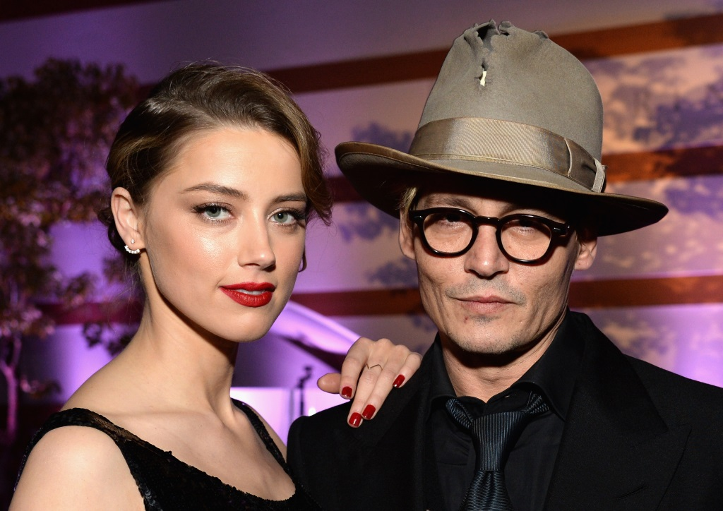 Amber Heard and Johnny Depp pose together and her hand is on his shoulder.