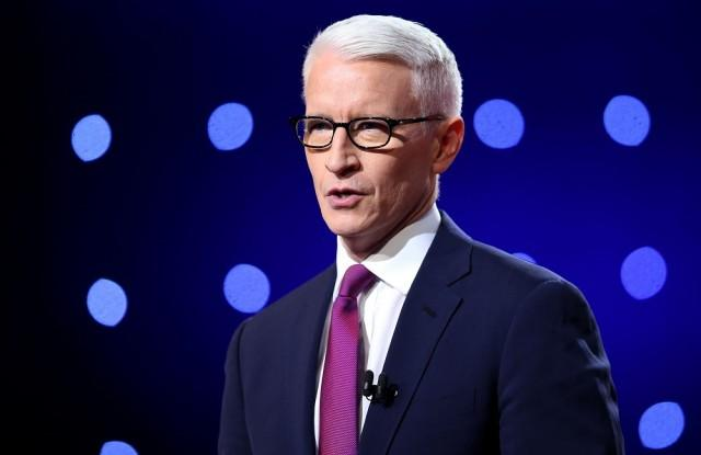 Anderson Cooper stands in a blue suit and purple tie while speaking to an audience.