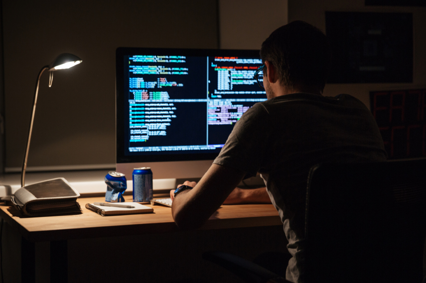 computer programmer writing code on computer