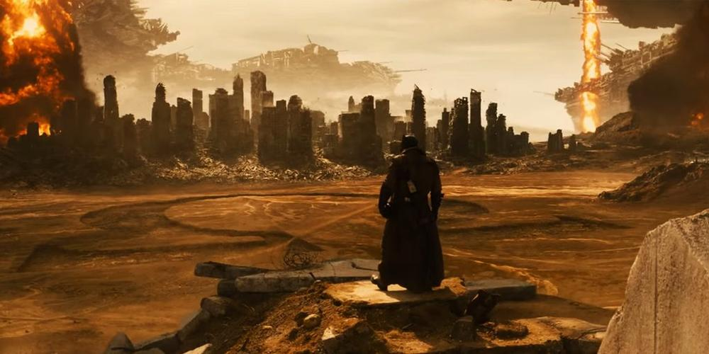 A figure in all-black stands in a deserted landscape and looks at a city ahead