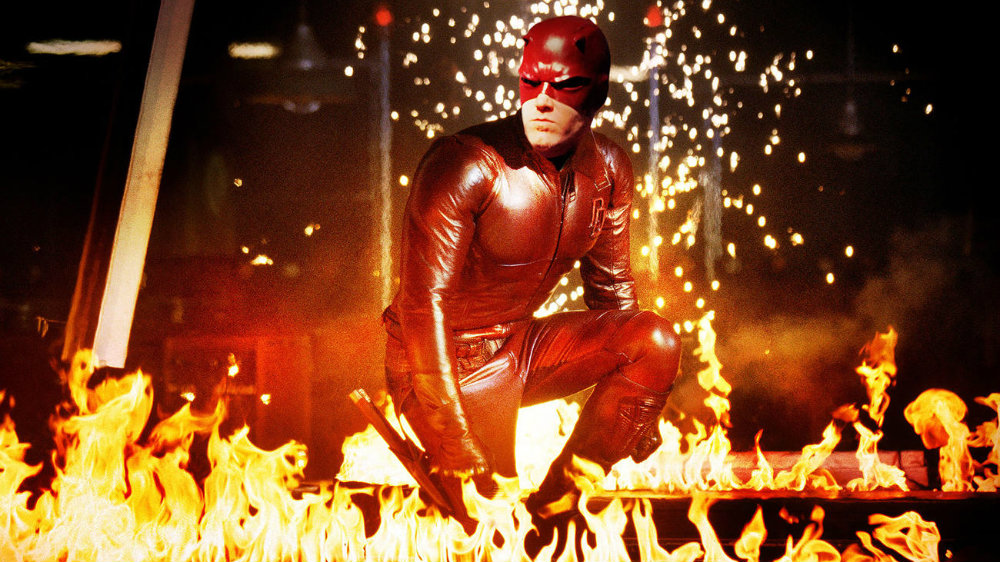 Ben Affleck suited up in a red costume in 'Daredevil' crouching amid flames