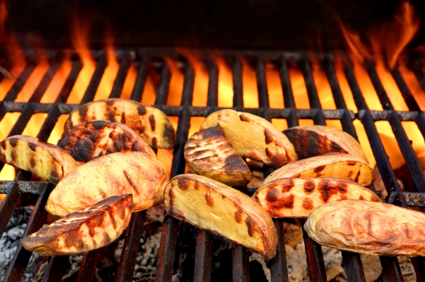 slices of potato on the grill with flames