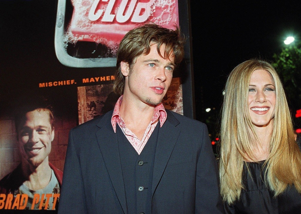 Brad Pitt with Jennifer Aniston in front of a Fight Club poster