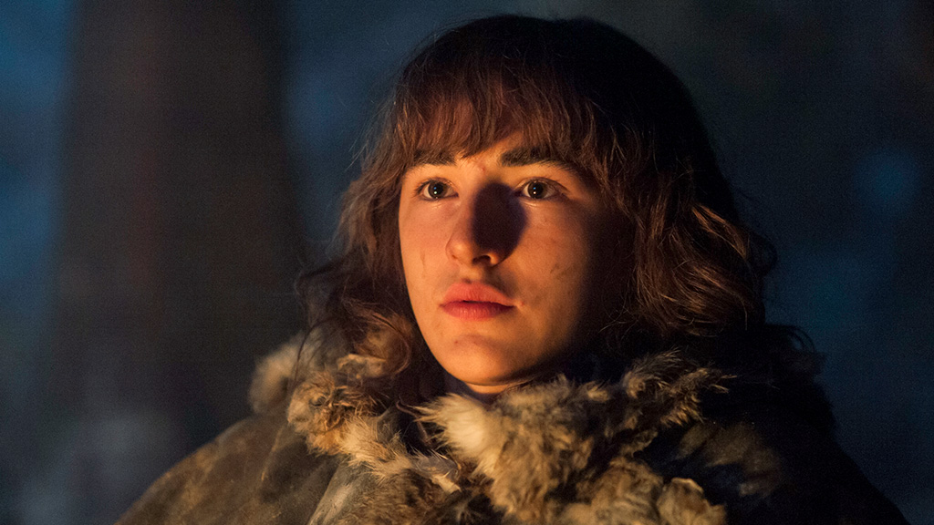 Bran Stark, looking to the left of the frame, and lit by the flame of a campfire