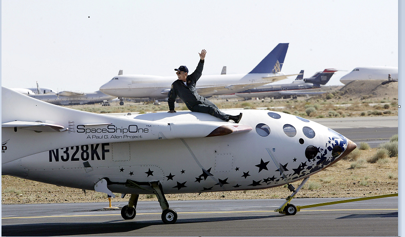 Test pilot Michael Melvill rides atop of SpaceShipOne as it is towed down the runway