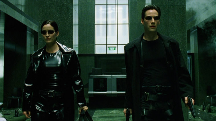 Carrie-Anne Moss and Keanu Reeves standing side by side dressed in black in The Matrix
