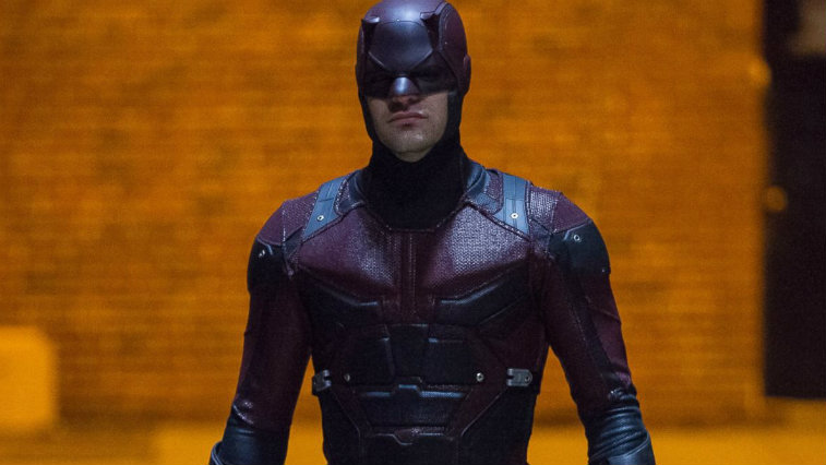 Charlie Cox wearing the full Daredevil outfit, against an orange-lit brick wall