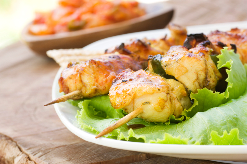 close-up of chicken skewers on a bed of lettuce with a tomato relish in the background